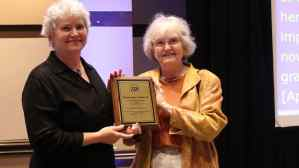 Two white women with white hair standing next to each other holding a plaque with TDI logo and text.