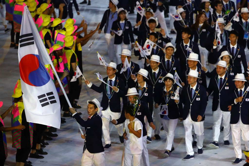RIO DE JANEIRO, BRAZIL - AUGUST 05:  Flag bearer Bongil Gu of the Republic of Korea leads his team during the Opening Ceremony of the Rio 2016 Olympic Games at Maracana Stadium on August 5, 2016 in Rio de Janeiro, Brazil.  (Photo by Elsa/Getty Images)