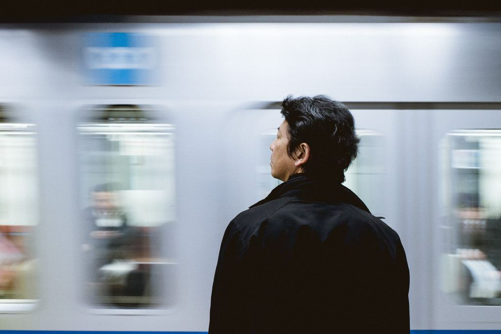 Man watching the blurred train stop at Yokohama station.