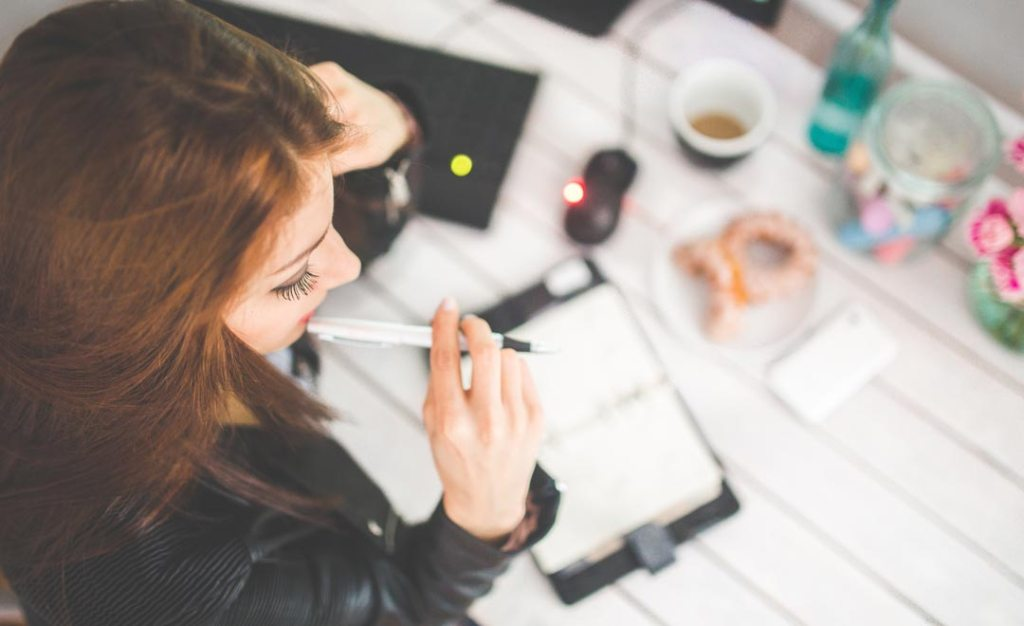 Woman changing focus to more me-time. Image shows women at desk from above, pen in mouth, and stuff on her desk out of focus.