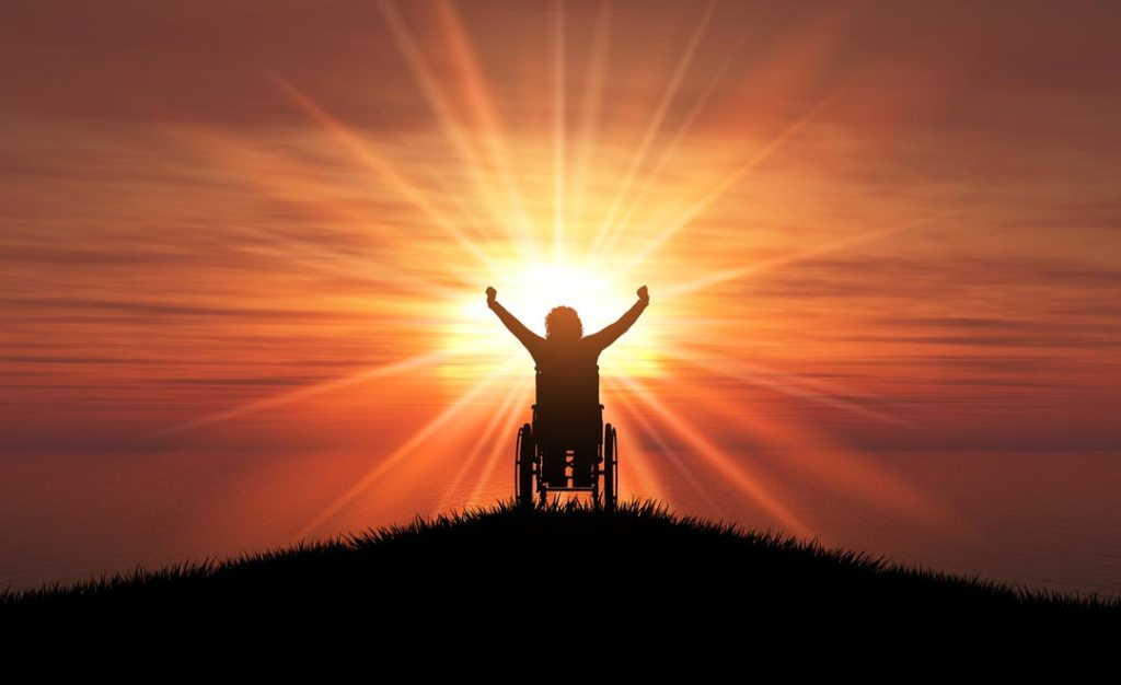 Inspiration porn! Silhouette of person in wheelchair with hands raised in triumph. And a background of a radiant orange sun.
