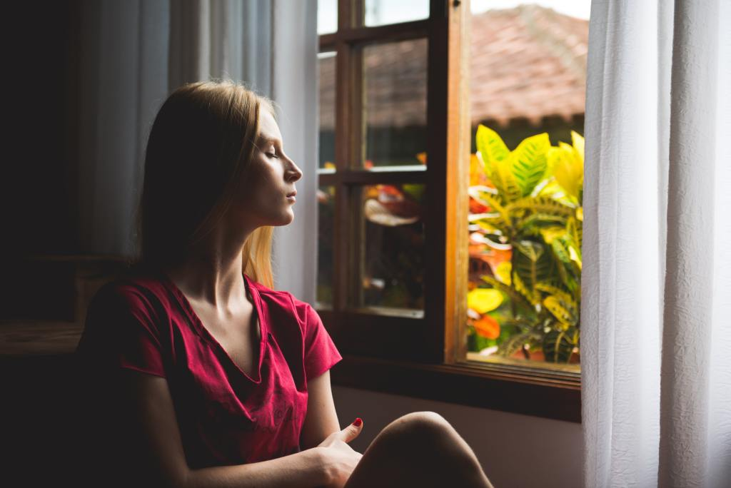 Woman gazing out an open window