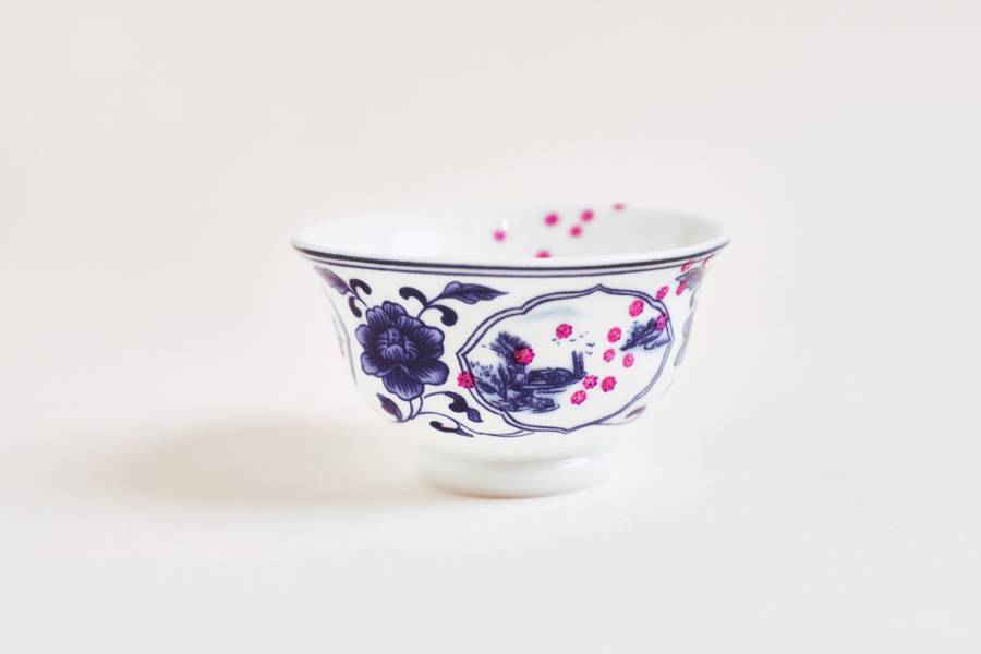 Coronavirus Tea Chinese Teacup, a blue & white china teacup spattered with pink dots of Covid-19