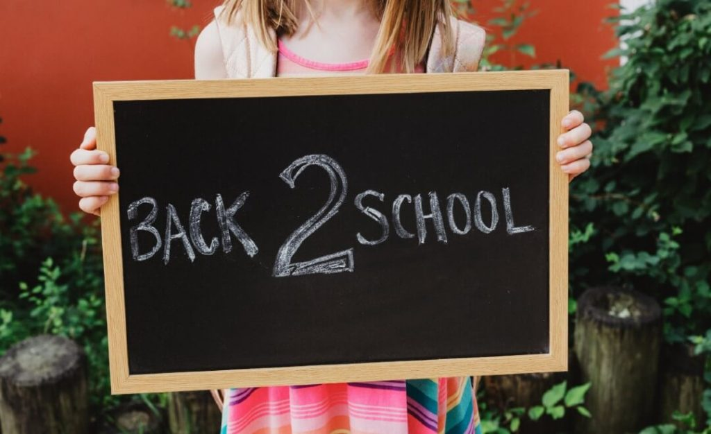 "Homeschooling: A girl holing a small chalkboard that says ""Back 2 School"""