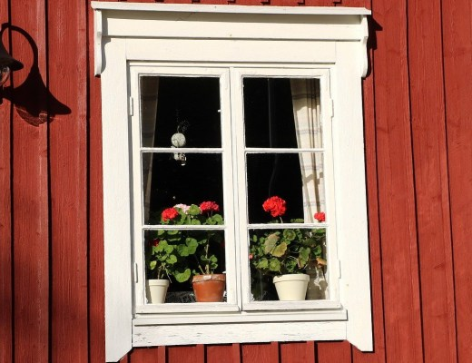Going north and going tiny, image of window in a red-sided cottage