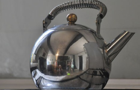 A silver kettle on a gas stove
