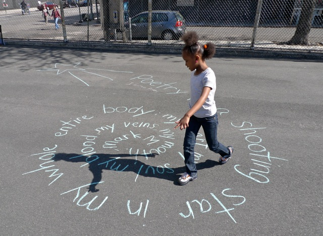 A child walks along a path of words in a spiral written in chalk on the pavement.