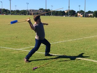 Student throwing the atlatls, a Native American spear-throwing device