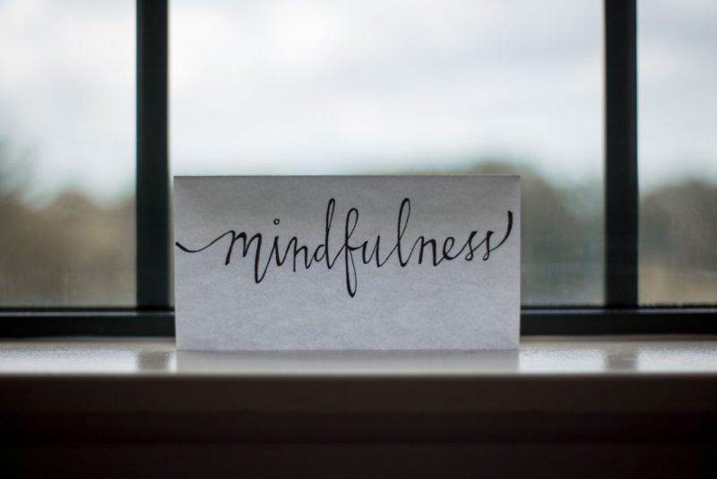 a white sign sitting on a windowsill with the word mindfulness written in script on it to remind me to focus on teacher self-care.  You can see clouds and a large tree in the distance.