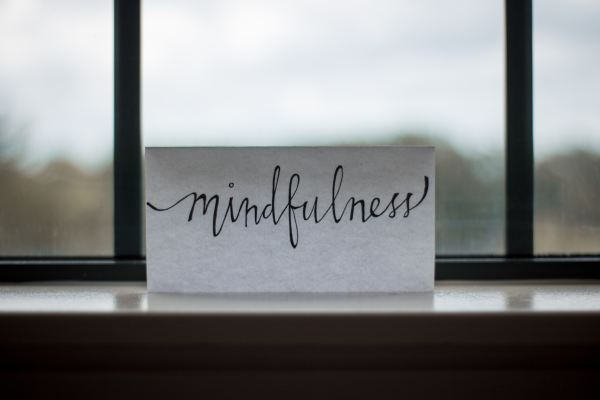a white sign sitting on a windowsill with the word mindfulness written in script on it to remind me to focus on teacher self-care.