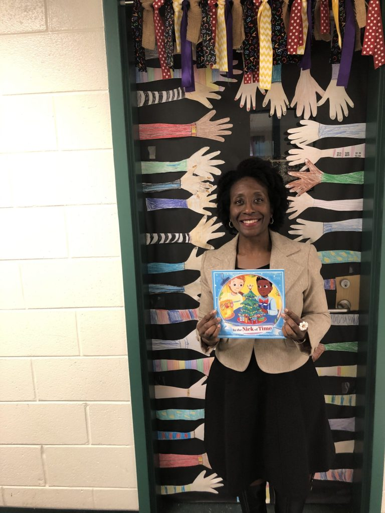Photograph of a smiling African-American woman standing in front of a door that is covered with black paper and multicultural hands.  She is holding a book, In the Nick of Time, in her hands.