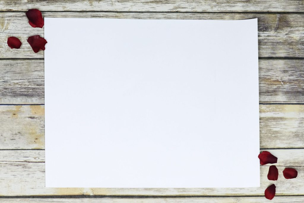 image of a plain, white sheet of paper on top of a wooden floor.  There are a sprinkling of rose petals at the top, left corner and the bottom, right corner.