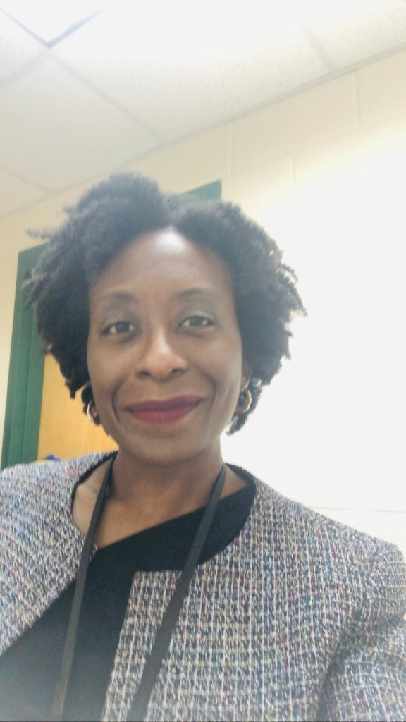 An image of Tania N. Davis of Teach Me T.  A smiling, brown-skinned, African American woman with natural, short hair.  Wearing a woven, multi-colored jacket over a black shirt, with a lanyard around my neck.