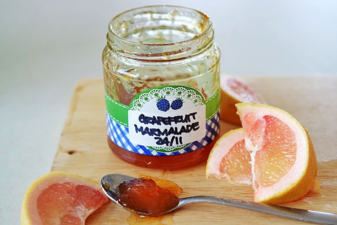 Finished Jar of Grapefruit Marmalade sitting on a board, open, with fresh wedges of grapefruit.