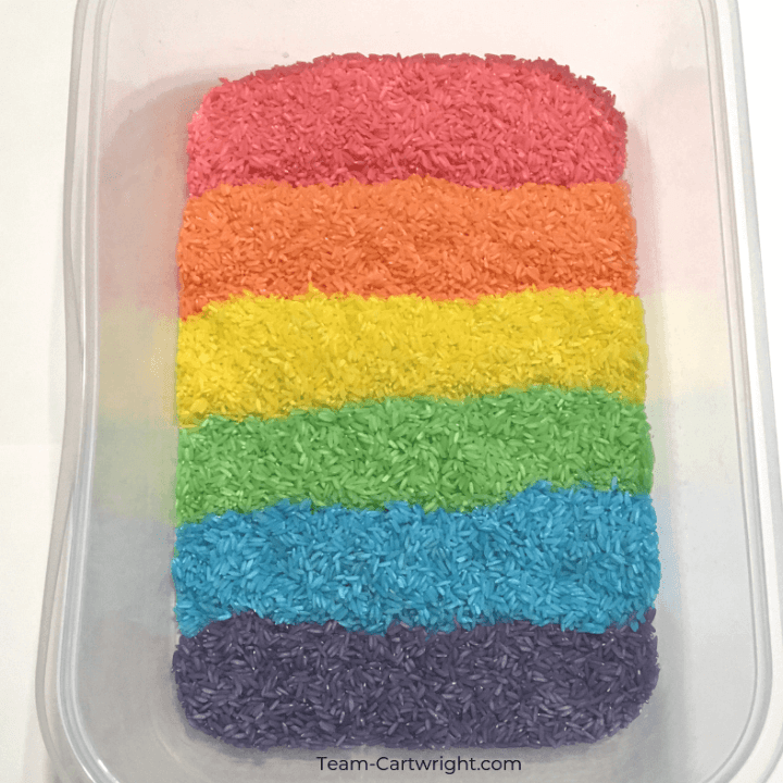 Colored rice for rainbow sensory play! Learn how easy it is to make this colorful sensory bin and get even more sensory activity ideas. #SensoryPlay #SensoryBin #ColoredRice #RainbowRice #RainbowSensory Team-Cartwright.com