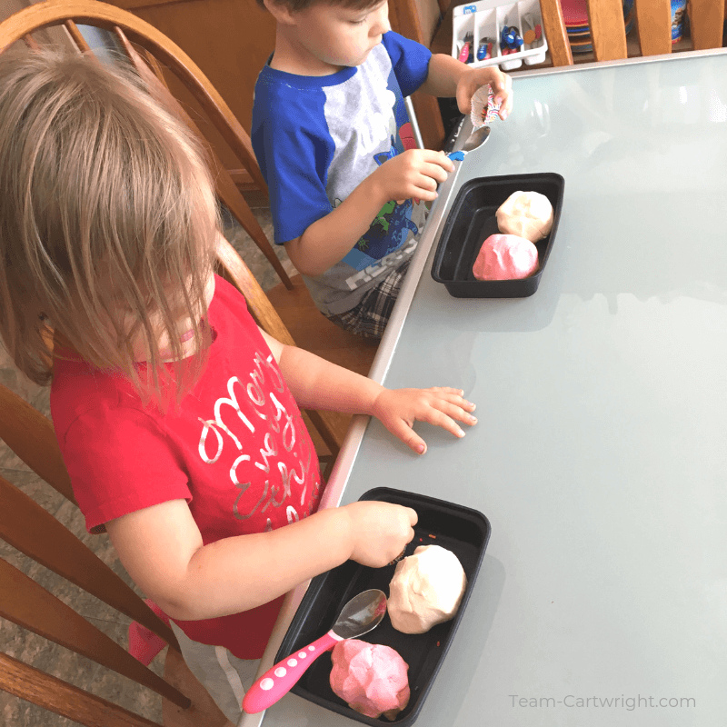picture of toddler girl and preschool boy playing with ice cream playdough at a table