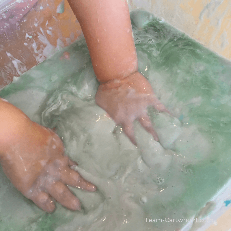 picture of a child's hands in a messy sensory bin