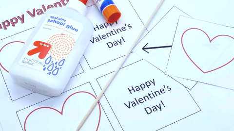 picture of free printable thaumatrope valentines, skewer for making them, liquid glue, and a glue stick