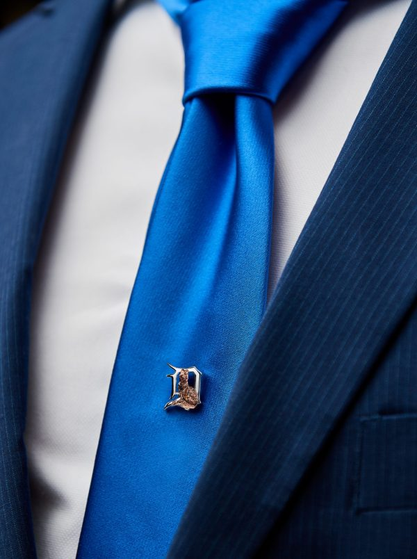 a small fox lapel pin on a suit tie