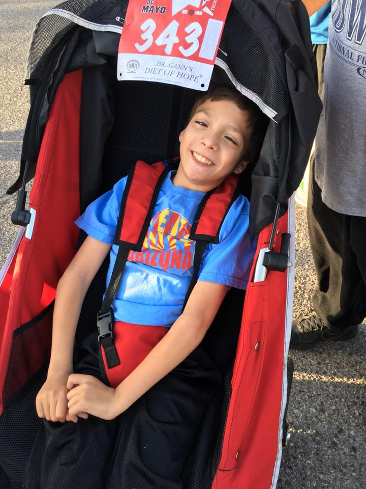 A boy (Christian) in his race wheelchair smiling a big smile. He is wearing the blue Team Hoyt Arizona shirt with our gold and red picture.