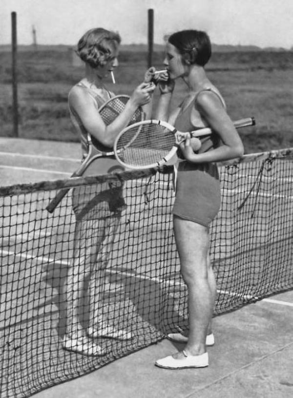 Vintage b&w pic of tennis playing women lighting cigarettes at net
