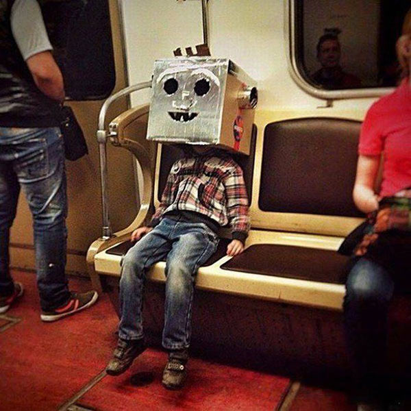 funny pic of boy with cardboard and foil box robot head riding subway