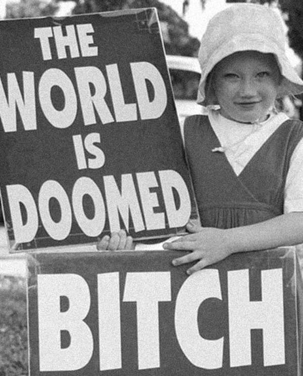 "Funny vintage pic of girl holding ""world is doomed, bitch"" signs"