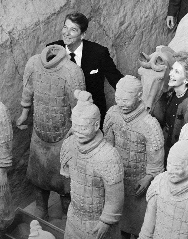 U.S. President and jokester Ronald Reagan poses behind a headless Terra Cotta Warrior as wife Nancy looks on. Xian, China, 1984.