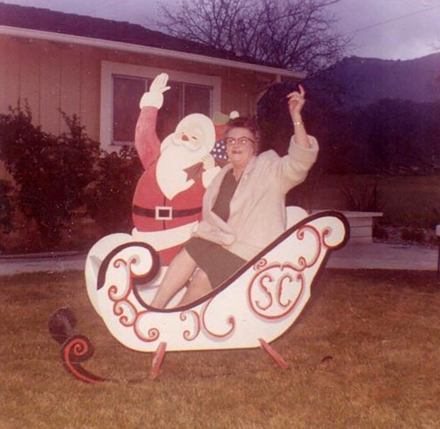 31 Awkwardly Funny Family Christmas Photos~ vintage snap 2960s woman in sleigh waving with Santa
