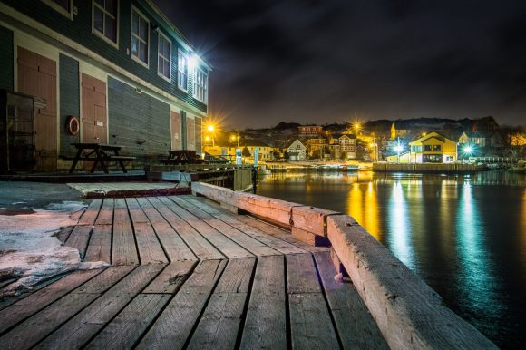 brown wooden dock near body of water during night time