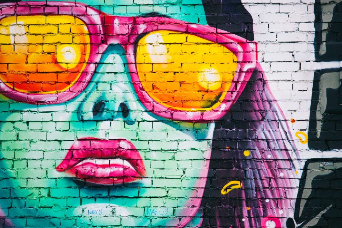 woman wearing sunglasses wall graffiti