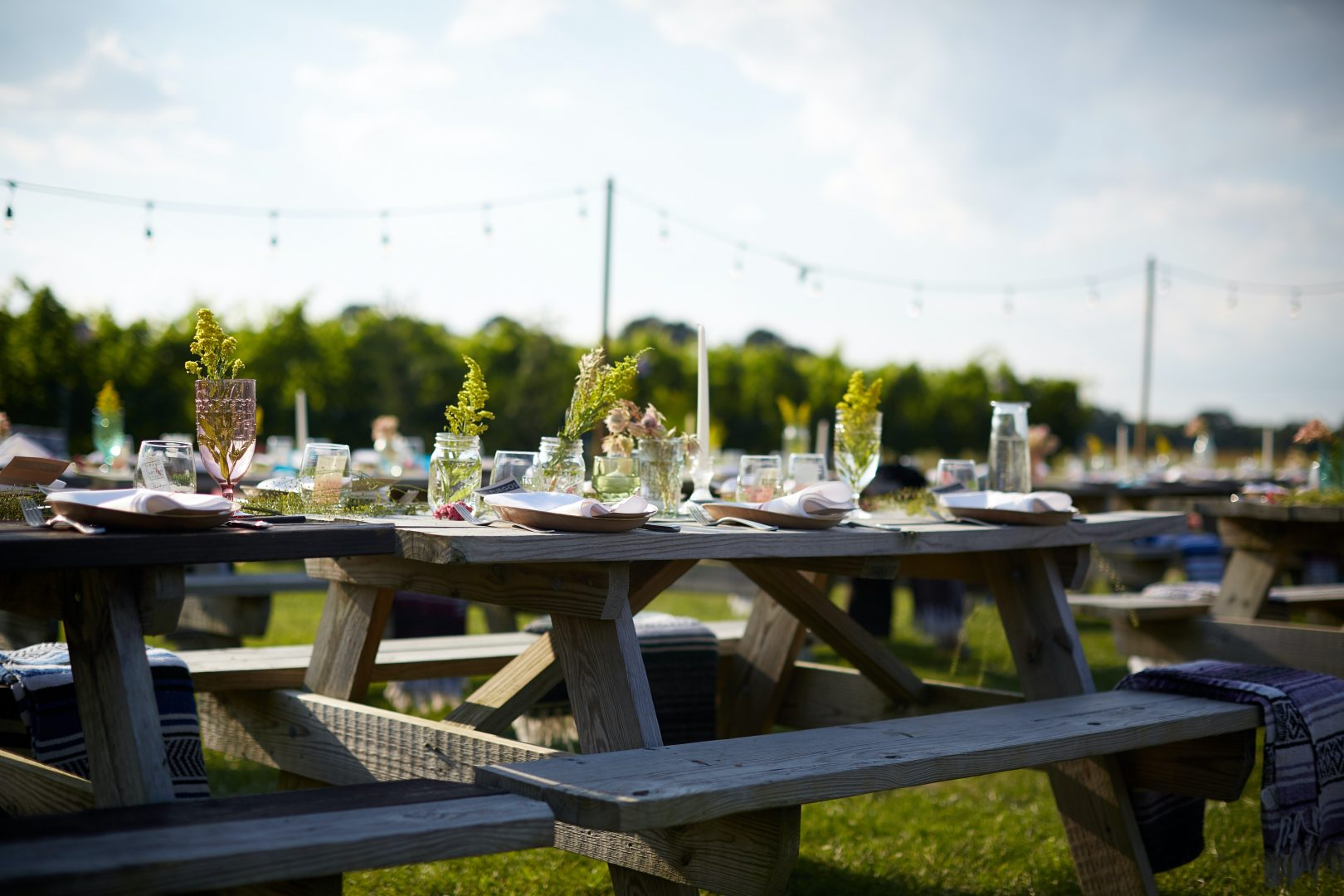 brown wooden table with chairs on green grass field during daytime