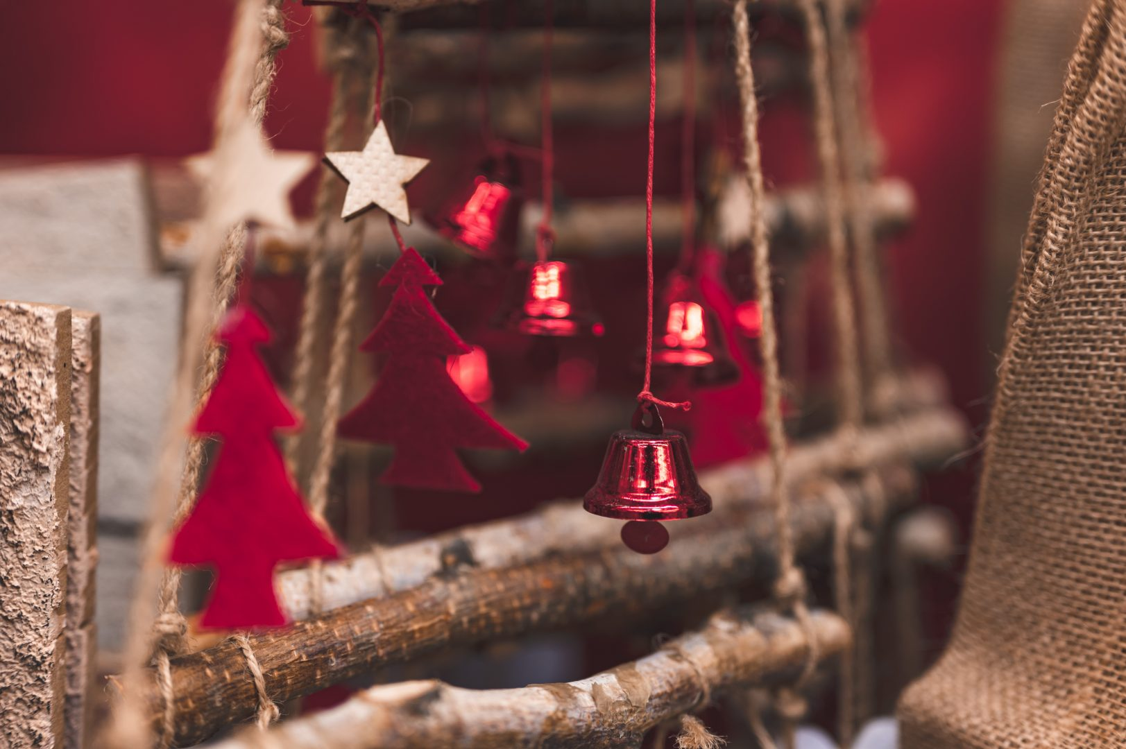 red and silver bell hanging on brown tree branch