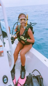 girl in scuba gear sitting on the edge of the boat