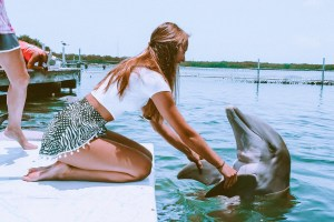 """girl holding """"hands"""" with a dolphin at the Dolphin Research center in the Florida Keys"""