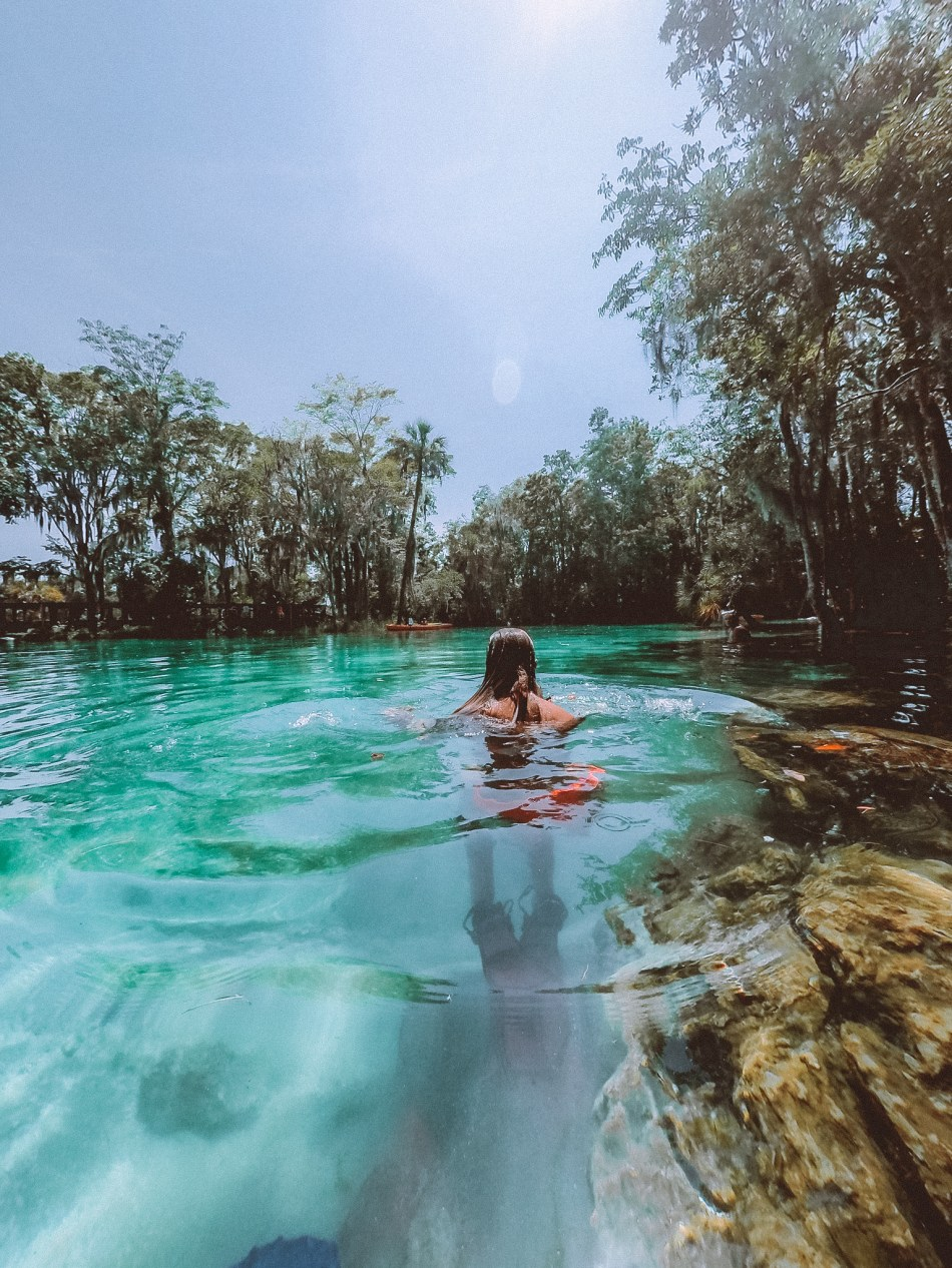 girl standing in crystal clear water at three sisters springs in florida