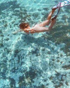 girl snorkeling in crystal clear water with pink fins in one of florida's natural springs