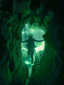 girl scuba diving at Blue Springs in Florida holding onto either side of a cavern, with the light behind her