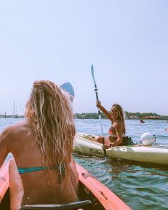 photo taken from the rear seat of a tandem kayak with girl in front seat facing away, and girl in single kayak in background of image smiling towards camera on crystal river in florida