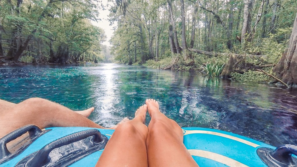 legs floating on a tube along a crystal clear spring river in florida