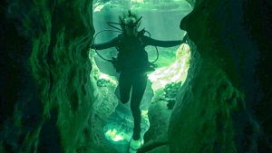 girl in scuba equipment looking into a cave underwater in Blue Springs, Florida