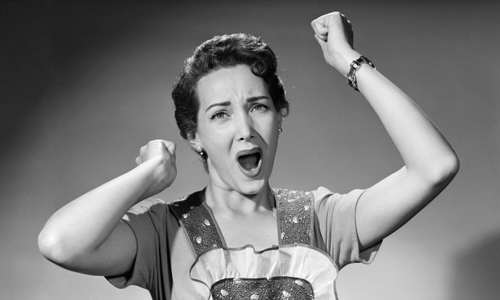 1950s woman in apron ruffled edge fists up in air yelling screaming angry housewife