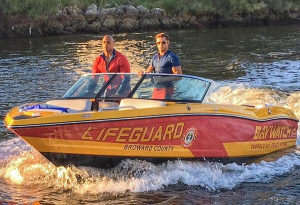 Dwayne Johnson and Zac Efron cruising around in a lifeguard speed boat. - Baywatch movie