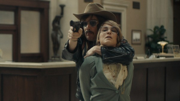 Ethan Hawk and Noomi Rapace in the movie Stockholm - Lars (ETHAN HAWKE) with his arm around Bianca (NOOMI RAPACE) pointing gun at police during negotiations in the bank lobby in STOCKHOLM.