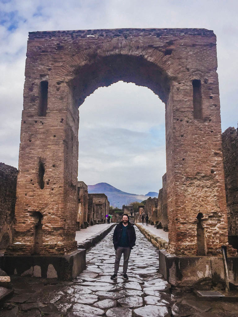 Colin standing under the giant arch at Pompeii with Vesuvius in the background
