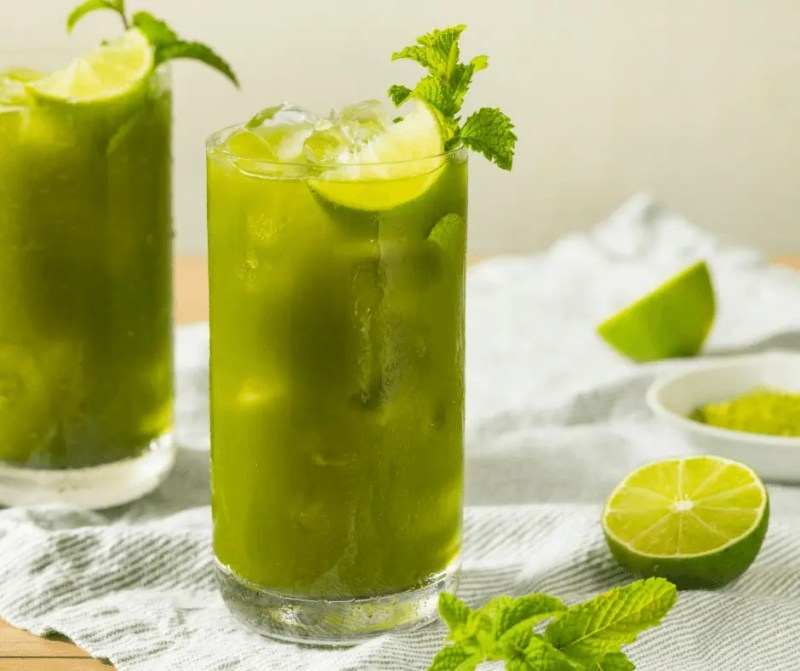 photo of a cocktail called Spiked Matcha Lemonade. It is in a tall glass, with lime wedge and mint for garnish.