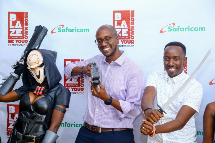 Safaricom Director Consumer Business Unit Charles Kare (Middle) in company of Standard Group Senior Business Manager Kevin Gicheru (Right) enjoy their combat skill lessons from the grim-reaper represented costumer (Left), during the Safaricom Blaze e-sports tournament launch held at Safaricom headquarters.
