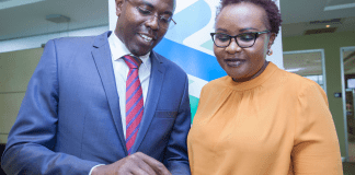 Standard Chartered Head of Wealth Management Kenya and East Africa Paul Njoki (left), takes the bank's Head of Retail Banking Kenya Edith Chumba through the T bills and Bonds trading process during the launch