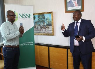 CEO NSSF Dr. Antony Omerikwa(right) is shown how to purchase scheme installments service charge through M-PESA by Austin Ouko General Manager NSSF (left), during the announcement of a partnership with Safaricom.
