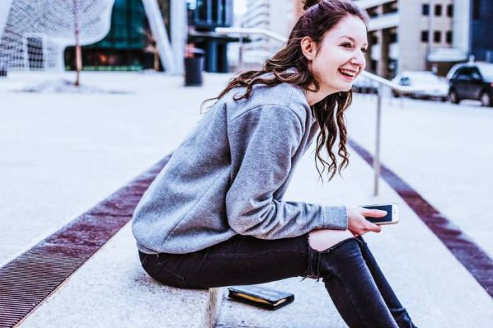 Smiling-Girl-Woman-Using-Smartphone-Apps-Social-Media-Street-Sitting-City-Urban-Outside
